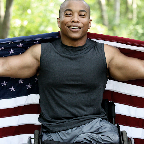 Persons with Disabilities Link Button Image -  a man in a wheelchair in front of a flag